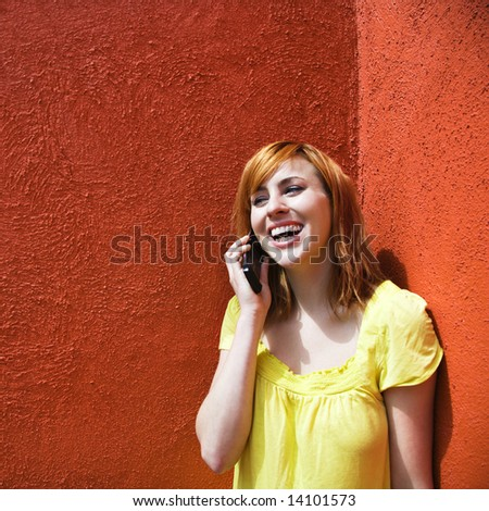 Smiling young redhead female talking on cellphone.