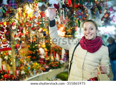 smiling  young russian woman choosing Christmas decoration at market in evening time