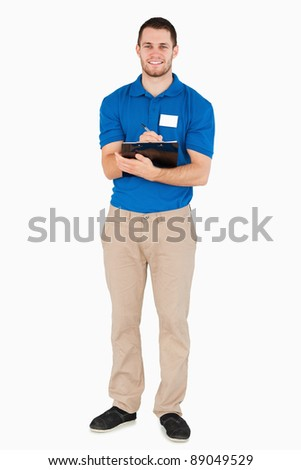 Smiling young salesman making a survey against a white background - stock photo