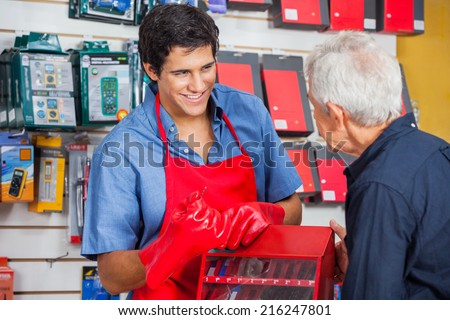 Smiling young salesman showing drill bit to senior man in hardware store - stock photo