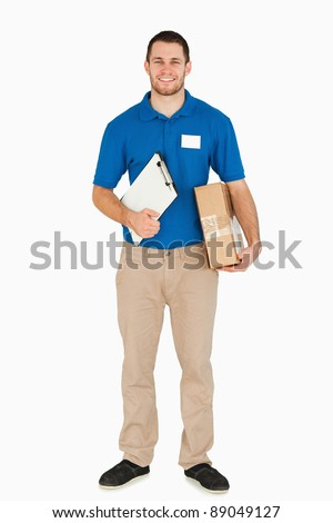 Smiling young salesman with clipboard and parcel against a white background - stock photo