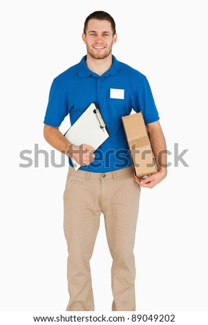 Smiling young salesman with packet and clipboard against a white background - stock photo