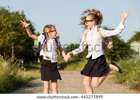 Smiling young school children in a school uniform jumping on the road in the park at the day time. Concept of the girls are ready to go to school. - stock photo
