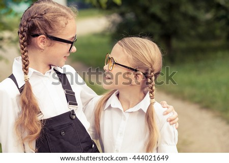 Smiling young school children in a school uniform standing against a tree in the park at the day time. Concept of the girls are ready to go to school. - stock photo