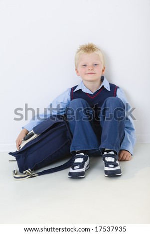 Smiling young schoolboy sitting on the floor with schoolbag. He's loking at camera, front view.