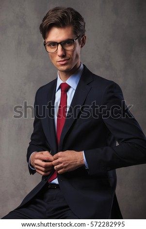 smiling young seated businessman buttoning his suit and looks at the camera in studio