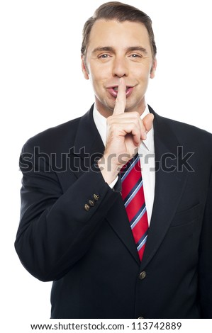 Smiling young smart business representative gesturing silence - stock photo