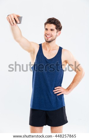 Smiling young sportsman standing and talking selfie with cell phone over white background