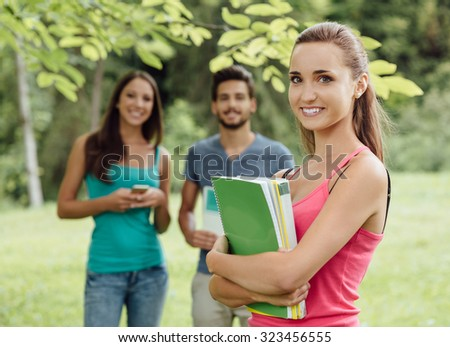 Smiling young student at the park holding books and notebooks, her friends are standing on background - stock photo