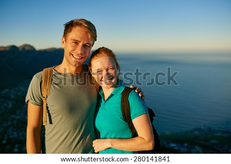 Smiling young student couple posing in morning sunshine while on a hike together