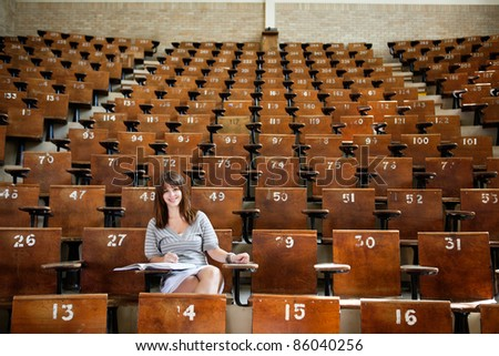 Smiling young student in empty lecture hall - stock photo