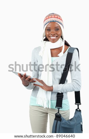 Smiling young student in winter clothes with her tablet against a white background - stock photo