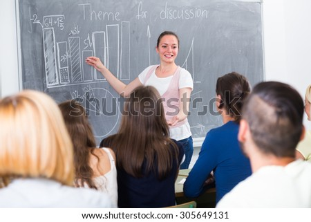 Smiling young student standing near blackboard in classroom