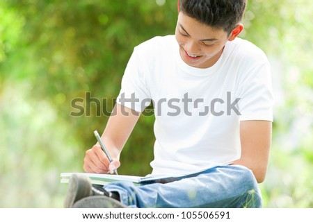 Smiling young student studying outside - stock photo