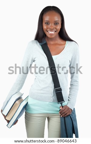 Smiling young student with books and bag against a white background - stock photo