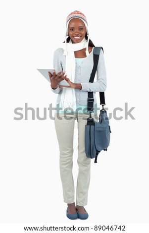 Smiling young student with scarf, hat and touchpad against a white background - stock photo