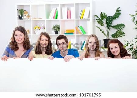 smiling young students holding big empty paper for commercials - stock photo