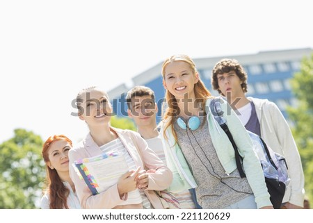 Smiling young students standing together at college campus - stock photo