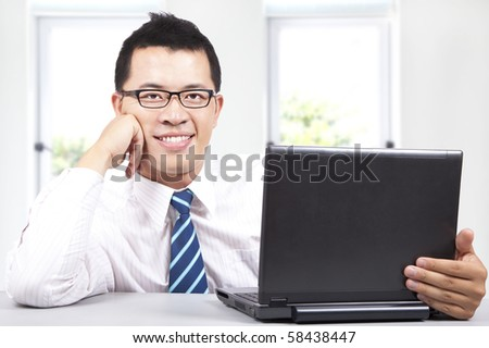 smiling young success businessman work with computer - stock photo