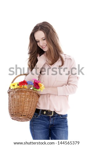 Smiling young teenage girl with a wicker basket of fresh flowers on her arm looking down at them with a smile, isolated on white