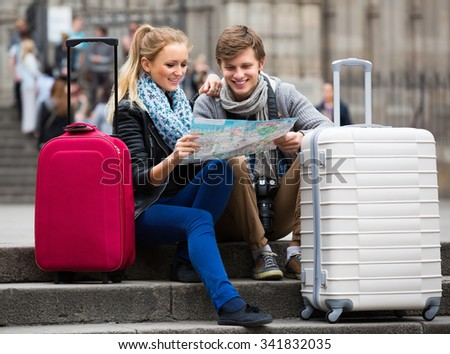 Smiling young travellers couple reading city map and looking for hotel