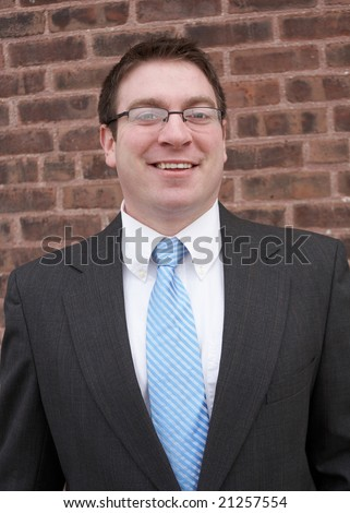 Smiling young urban businessman in front of brick wall - stock photo