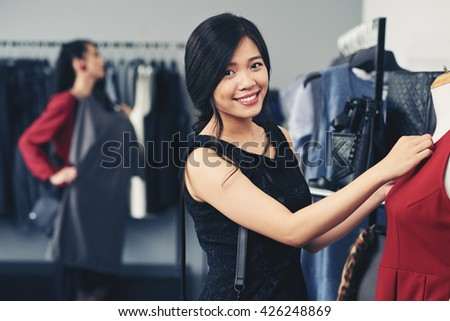 Smiling young Vietnamese woman choosing clothes in fashion boutique