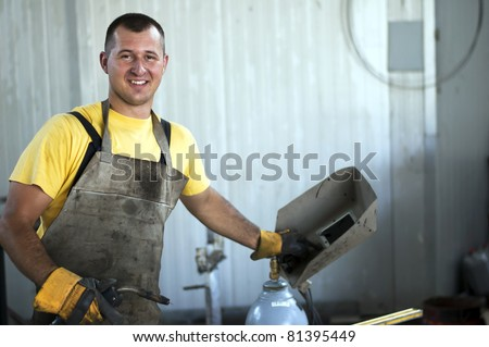 Smiling young welder at work - stock photo