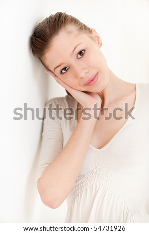 Smiling young woman about light wall. - stock photo