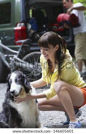 Smiling young woman and dog with blurred man loading car in the background - stock photo