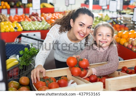 Smiling young woman and little girl shopping globe tomatoes in grocery  - stock photo