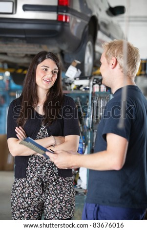 Smiling young woman and mechanic talking to each other in auto repair shop - stock photo
