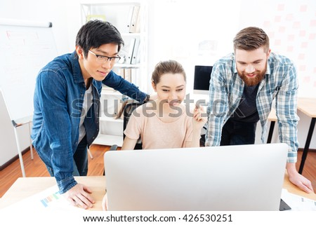 Smiling young woman and two handsome men working with computer in office together - stock photo