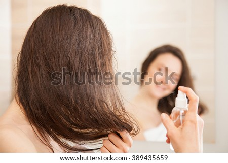 Smiling young woman applying hair spray in front of a mirror; haircare concept - stock photo