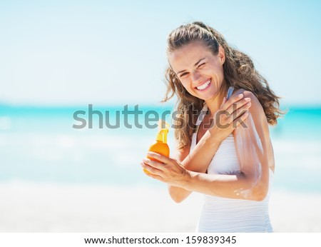 Smiling young woman applying sun block creme on beach - stock photo
