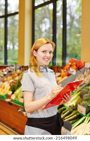 Smiling young woman as salesperson with clipboard in supermarkt - stock photo