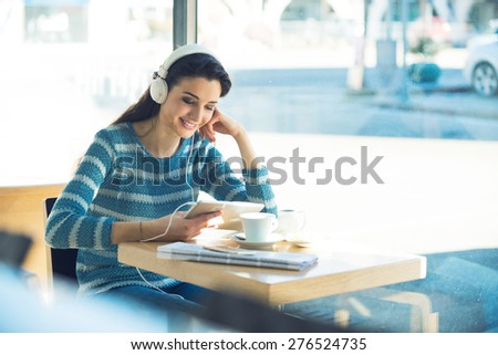 Smiling young woman at the cafe with headphones listening to music and using a tablet - stock photo