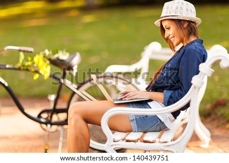smiling young woman at the park using laptop - stock photo