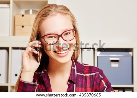 Smiling young woman calling with her smartphone at her office