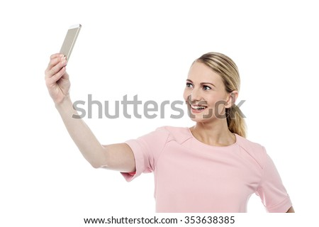 Smiling young woman capturing herself in her phone - stock photo