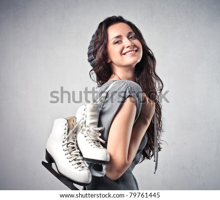 Smiling young woman carrying a pair of ice skates - stock photo