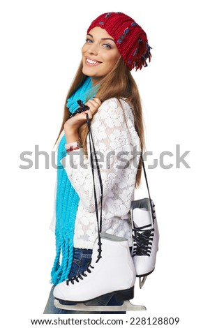 Smiling young woman carrying a pair of ice skates over white background - stock photo
