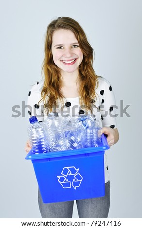 Smiling young woman carrying full recycling box on blue background - stock photo