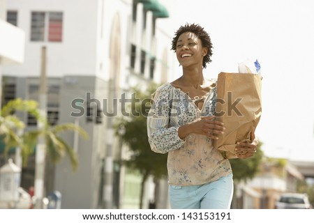 Smiling young woman carrying grocery bag while walking on street - stock photo