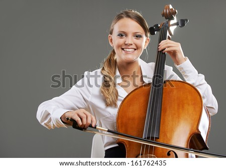 Smiling young woman cellist on grey background - stock photo