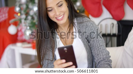Smiling young woman checking Christmas messages