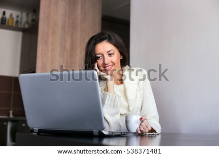 Smiling young woman checking her messages on laptop computer at home, with a cup of coffee in her hand