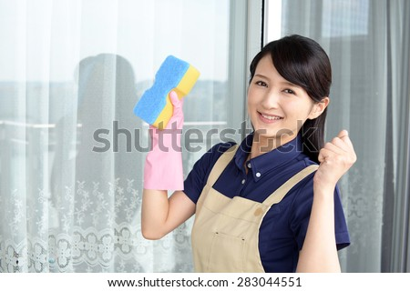 Smiling young woman cleaning the entrance. - stock photo