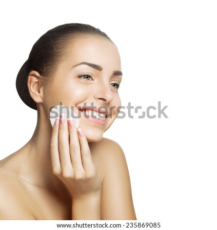 Smiling young woman cleans healthy skin and removes makeup cotton pad from the face on a white background