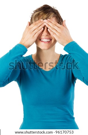 Smiling young woman covering her eyes with her hands. Studio shot against a white background. - stock photo